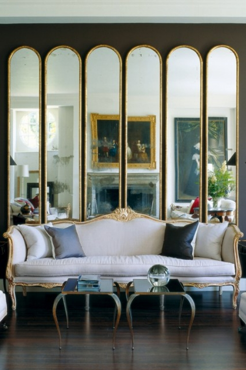 A line of the same mirrors placed next to each other create a fragmented reflection which really stands out against the dark walls. A very elegant and modern idea that enhances this traditional and classic room.   Image: houseandgarden.co.uk