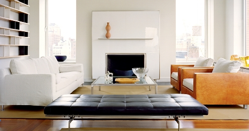 Steel framed white glass around the fireplace lightens and brightens this space and adds an extra element to the neutral decor. Softened with warm wood, soft tactile leather and low lying furniture. A very beautiful room based on modernist principles.   Image:1stdibs.com