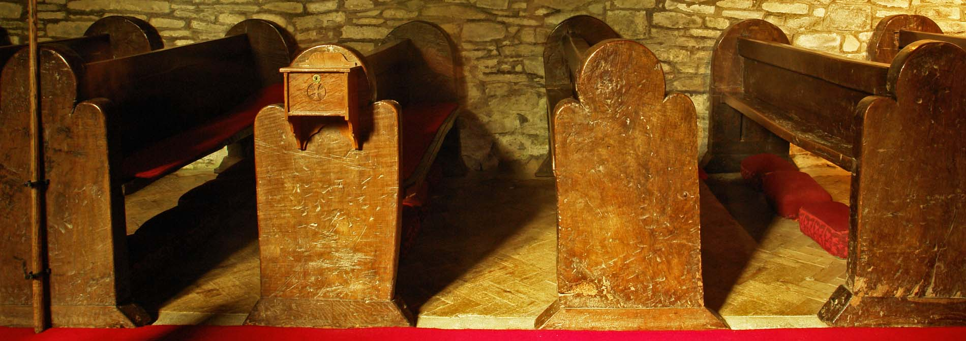 Roughly carved trefoil ended pews on the north side of the nave