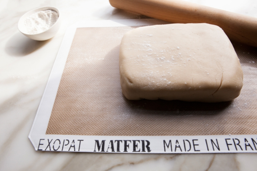 Forming the dough into a rectangular shape. Give the dough a light dusting of flour to prevent the rolling pin from sticking.
