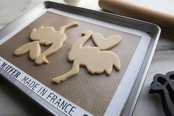 Once you have cut your cookies into desired shapes and removed excess dough, transfer entire silicone mat to baking sheet.