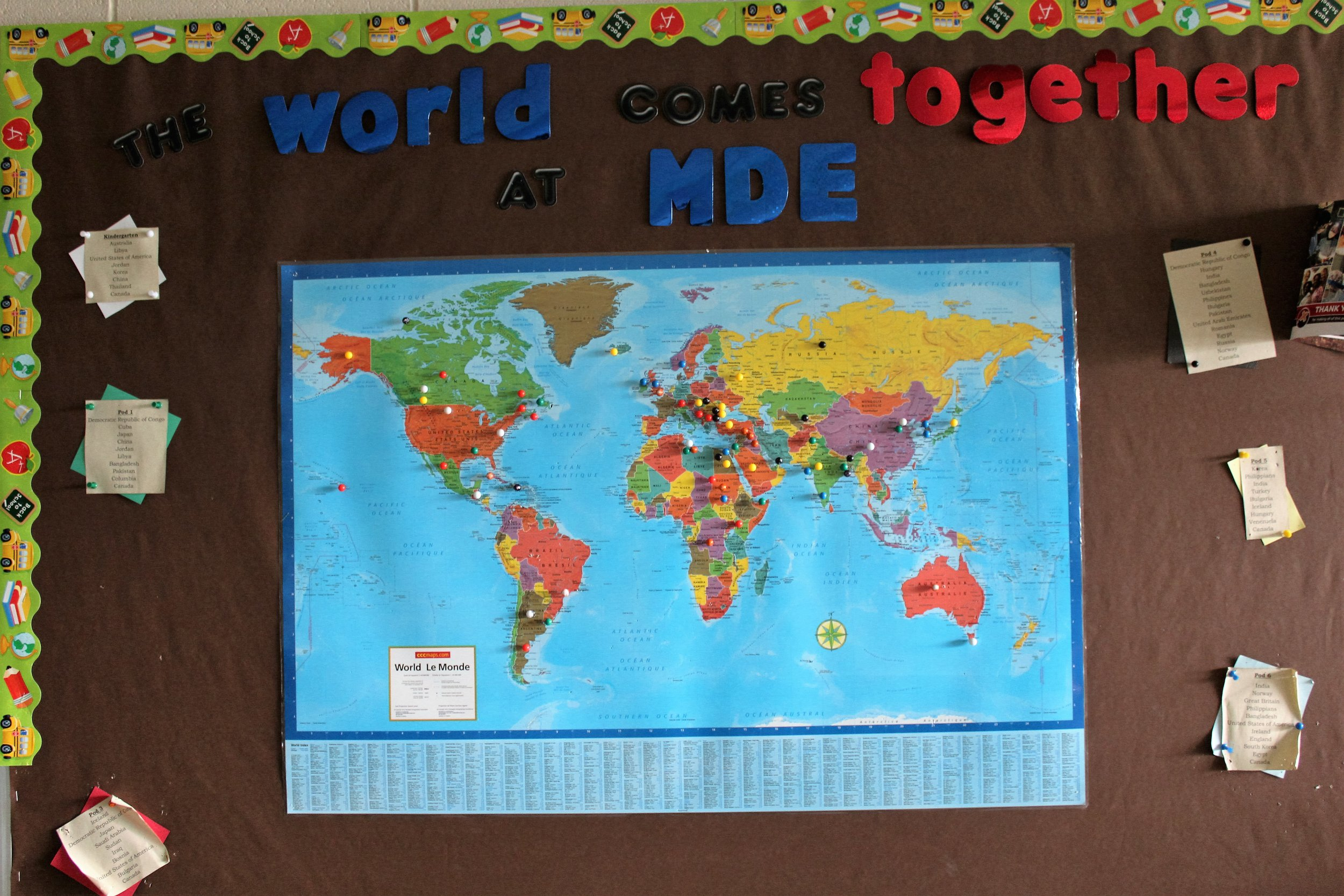 """The Bulletin Board in our main entrance changes every month or so. This month we are focusing on the many countries that make up the population of our school. All teachers discuss the variety of cultures and countries represented within their own classroom and then submit them to our gym teacher, who then represents the countries identified with colourful push pins on the map of the world. The caption: """"The World Comes Together at MDE"""" helps children to relate their unique connection within the school to that of the world, in general. Children from every classroom can be heard and/or seen pointing out their place in the world as well as commenting on all the places we represent in our own school.  This activity relates to global citizenship because it helps children to see how they, as a school, represent many of the countries in our world. It directly relates our diverse cultures to that of the world, in general. Pretty impressive to see. And, the student-generated comments and discussions related to it are reaffirming as they all feel interconnected and appreciated as members of our school."""