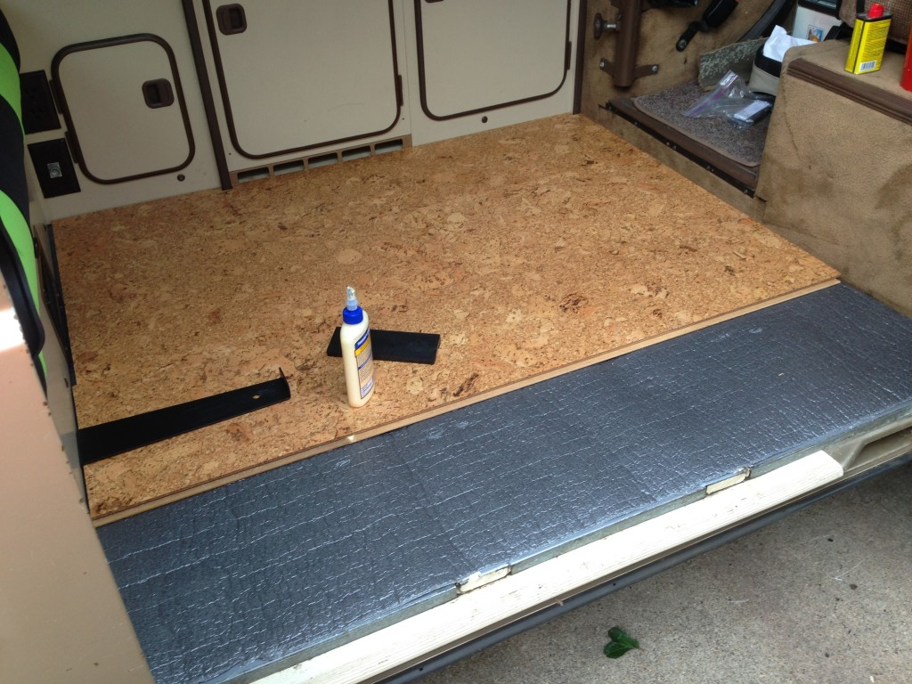 The cork floor installation with some soundproofing material installed underneath it. The two white rectangular spots you see at the edge of the gray are tracks for a third seat which we removed for this trip.