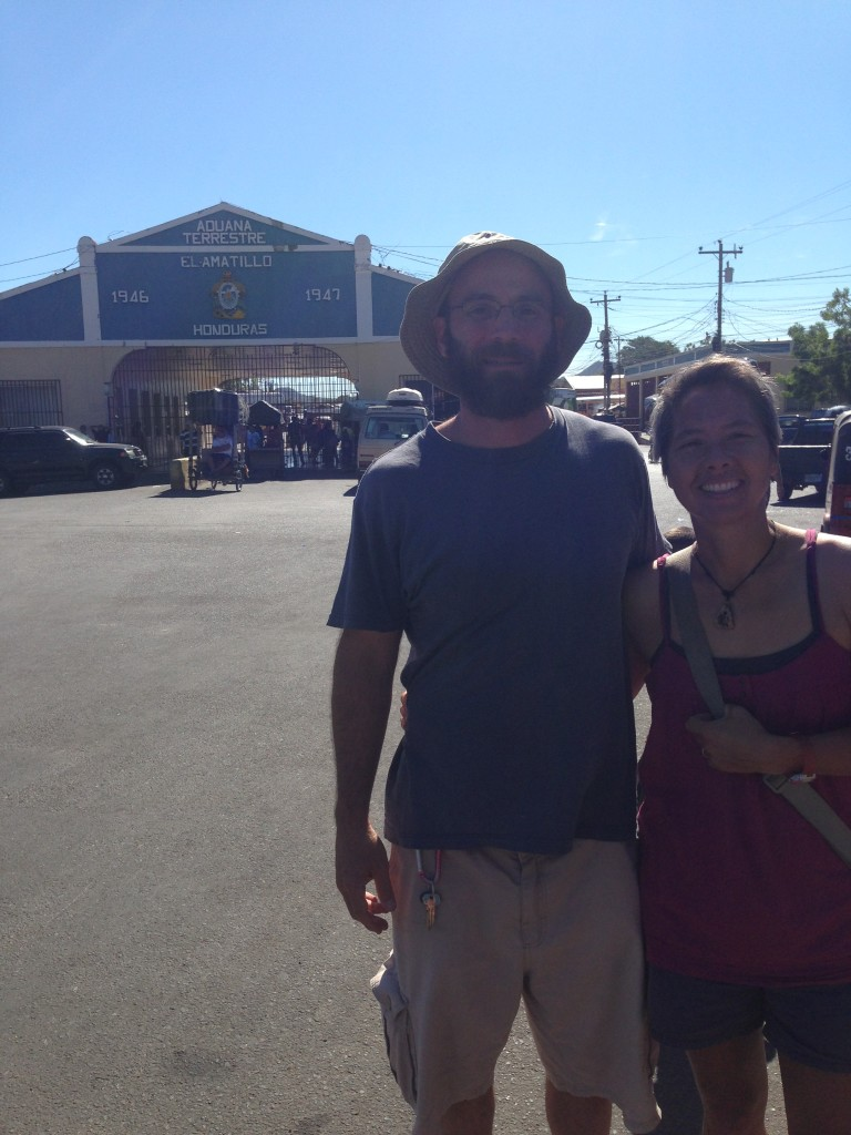 R and I pose at the El Salvador-Honduras border at 9 a.m. on another sweltering day while waiting for grilled meat on a stick.