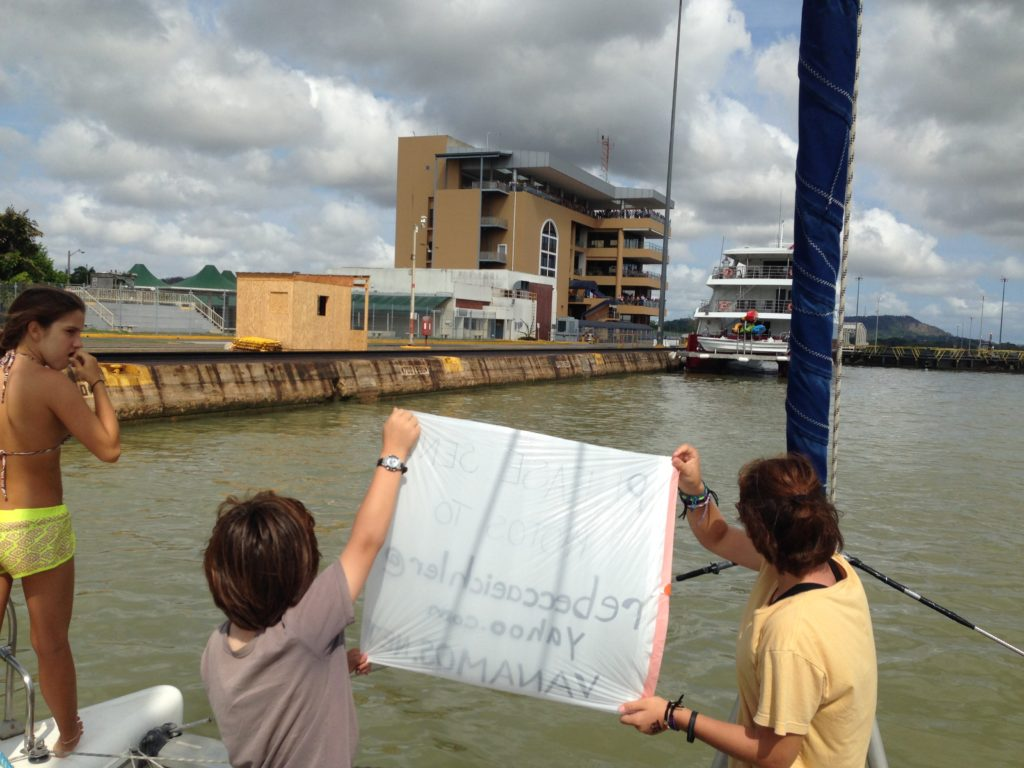 As we approached the Miraflores Locks and visitor center, Coconut and J held up a sign asking onlookers to email their photos to us.