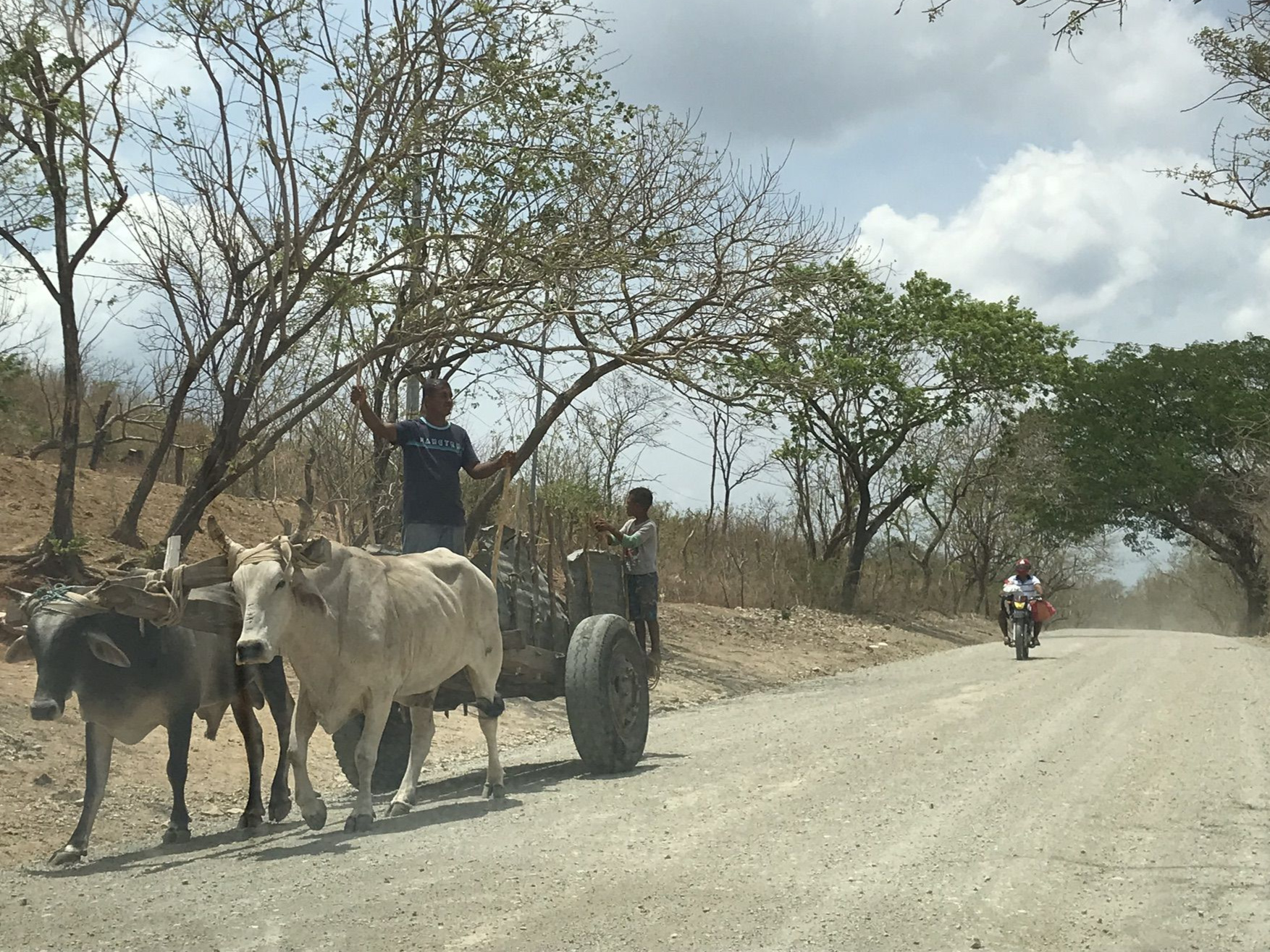 A cow-drawn cart being overtaken by a motorcycle on a dusty road is not an uncommon sight in Nicaragua or any country in Central America.