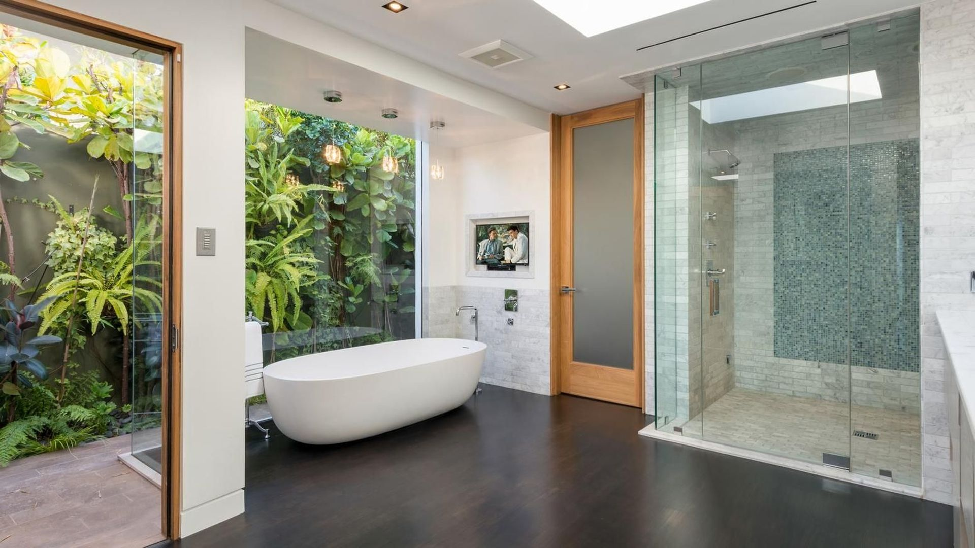 The master suite has a generous en suite and a wall of glass that leads directly out to the swimming pool.
