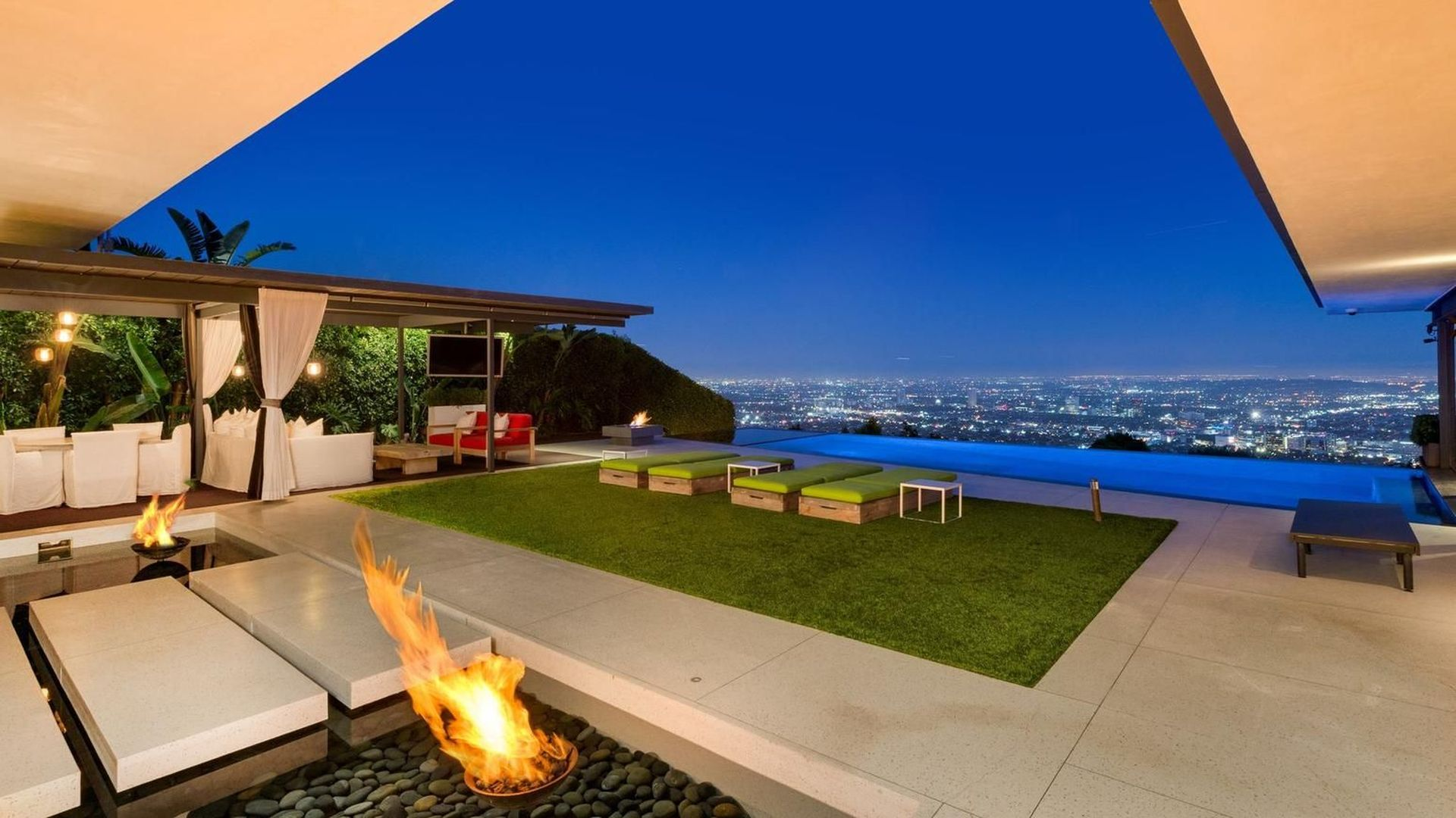The infinity pool is lit with led lighting and cascades down overlooking the city, with views that expand from Hollywood Hills over Downtown LA to the Pacific Ocean.