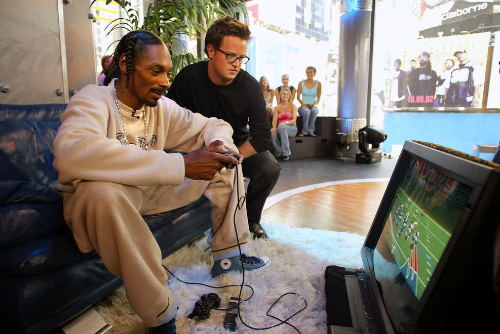 """Getty Images. Matthew Perry, during an appearance on TRL to promote his movie """"Serving Sara"""", watches Snoop Dogg play Playstation 2 at the MTV Studios in New York City."""