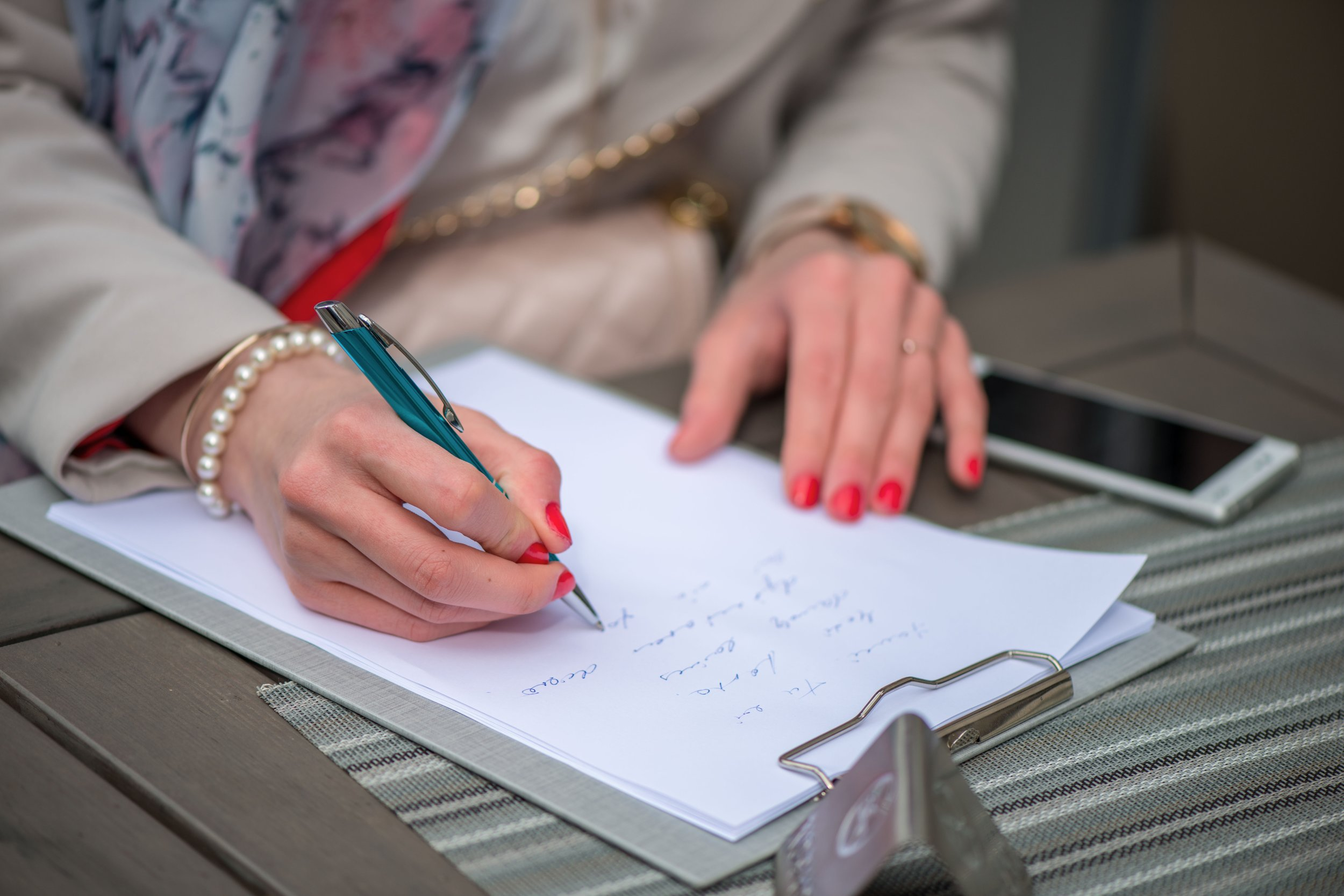 close-up-of-female-hands-woman-writing-something-sitting-at-cafe-signing-documents-woman-paperwork_t20_W7bm9m.jpg