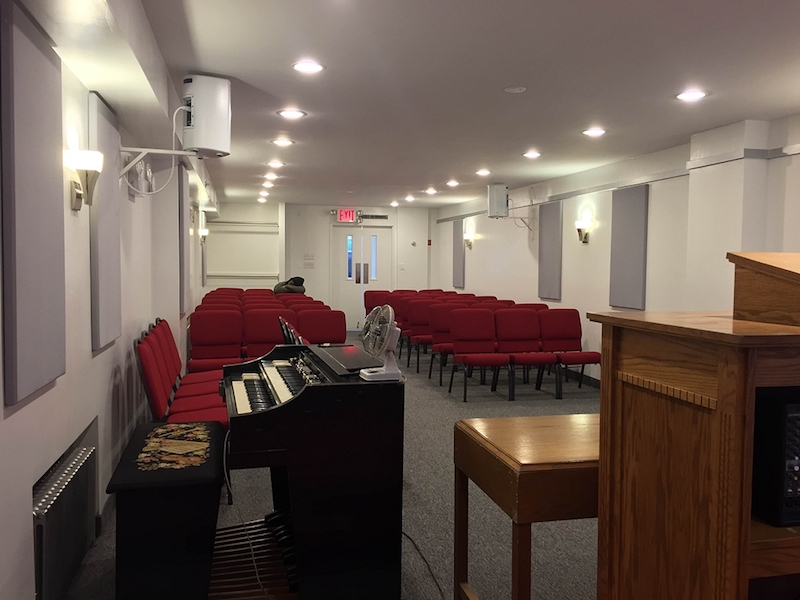 Interior of Bethlehem Moriah church hall with white walls piano and red chairs