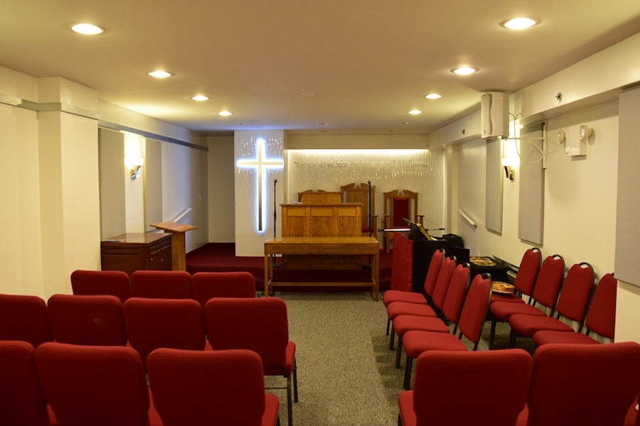 Interior of Bethlehem Moriah church hall with white walls piano and red chairs from the back looking at the altar
