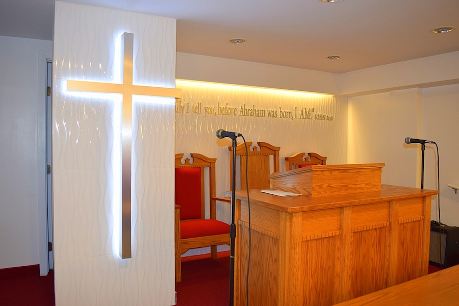 View of altar of Bethlehem Moriah church with illuminated cross at the front and wooden chairs