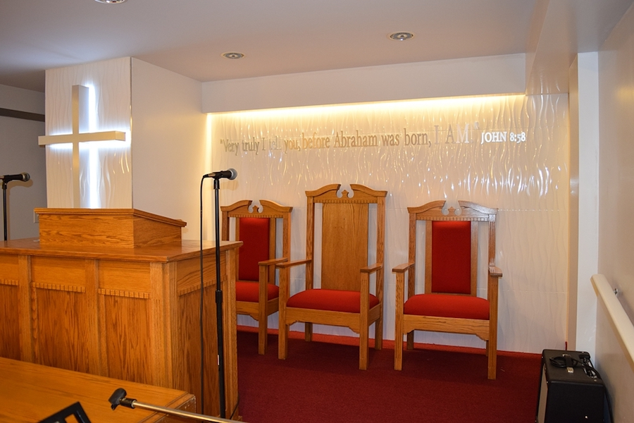 Wooden altar chairs at Christian church Bethlehem Moriah with altar and cross