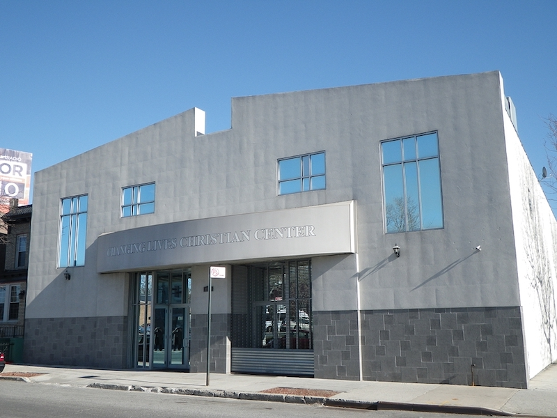 Exterior front view of new Changing Lives church with large glass windows dome entrance and blue sky