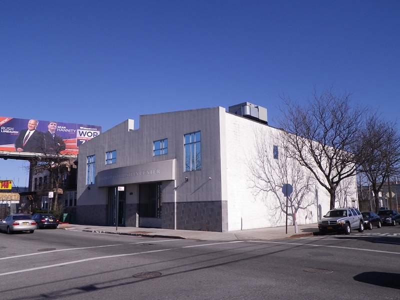 Exterior front view of new Changing Lives church with large glass windows and blue sky