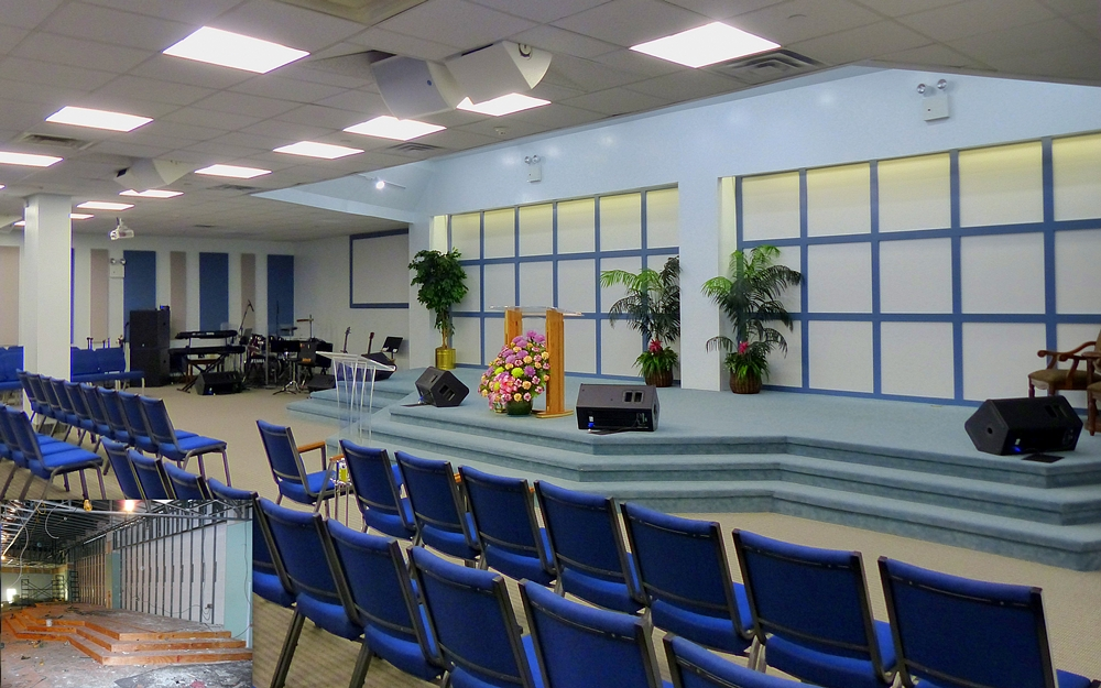 Interior of Christ Alive church with carpeted front altar area and blue chairs