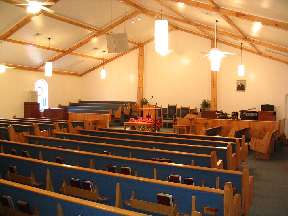 Interior of Emmanuel Baptist church after interior renovation with blue fabric lined pews in dim lighting