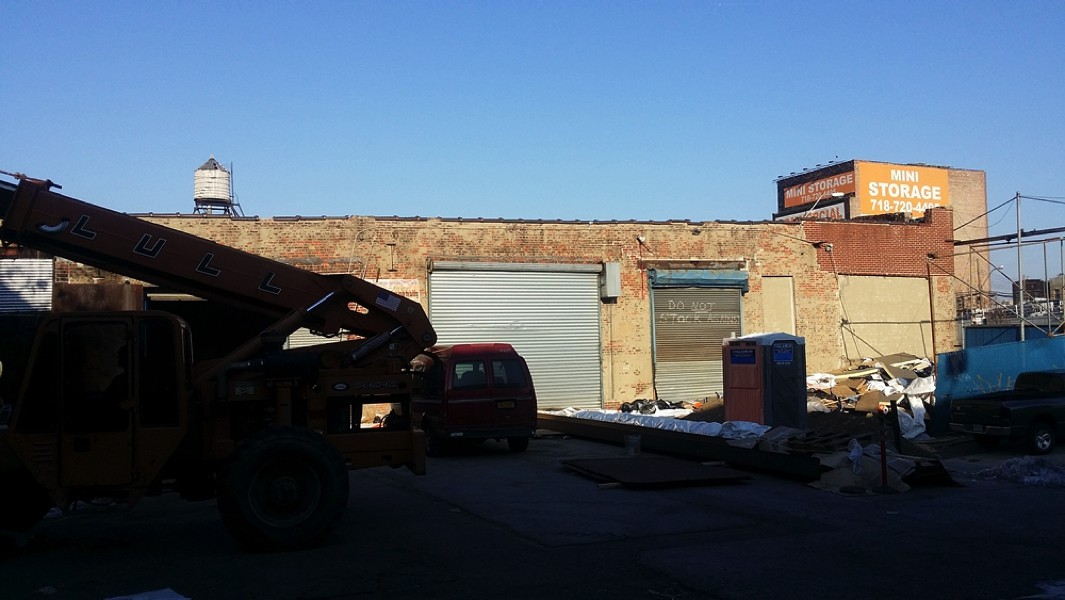 Back alley view of Grace International Church in abandoned boarded up brick building with garage doors in back