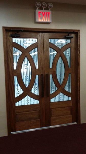 Intricately designed wooden door with interlocking curves at Grace International Church