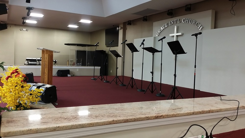 Choir section of Grace International Church with music stands and microphones and red carpeted area