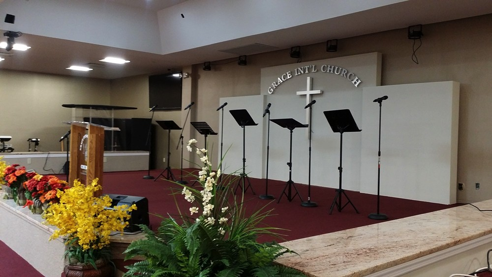 Choir section of Grace International Church with music stands and microphones