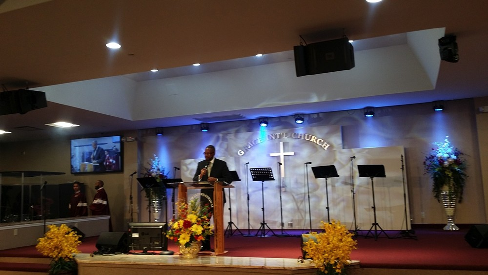 Preacher giving a sermon at Grace International Church with blue lights in the background