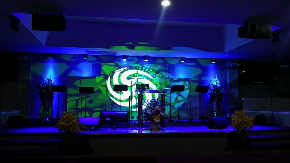 Podium of Grace International Church with blue strobe lights in modern church environment