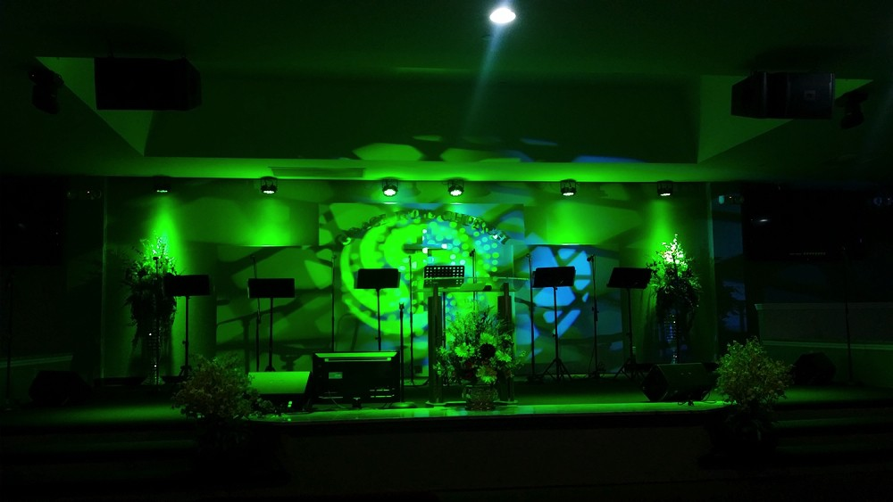 Podium of Grace International Church with green strobe lights in modern church environment