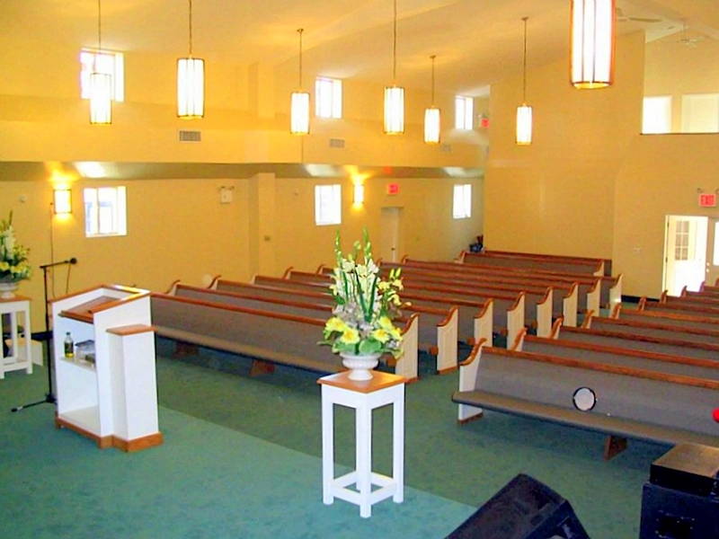 Interior view of Linden COGOP Church pews with flowers from front of room to back