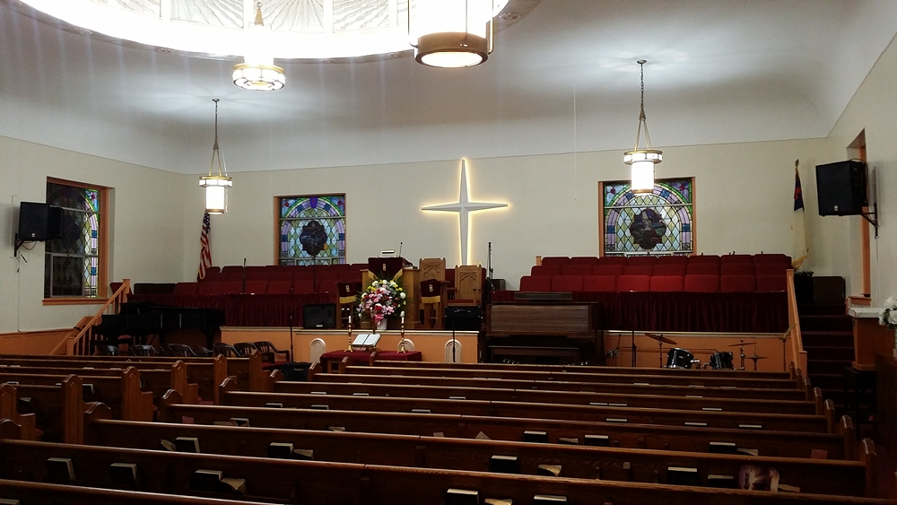 Interior of completed St. Johns Baptist Church with wooden pews and choir space behind podium and cross behind