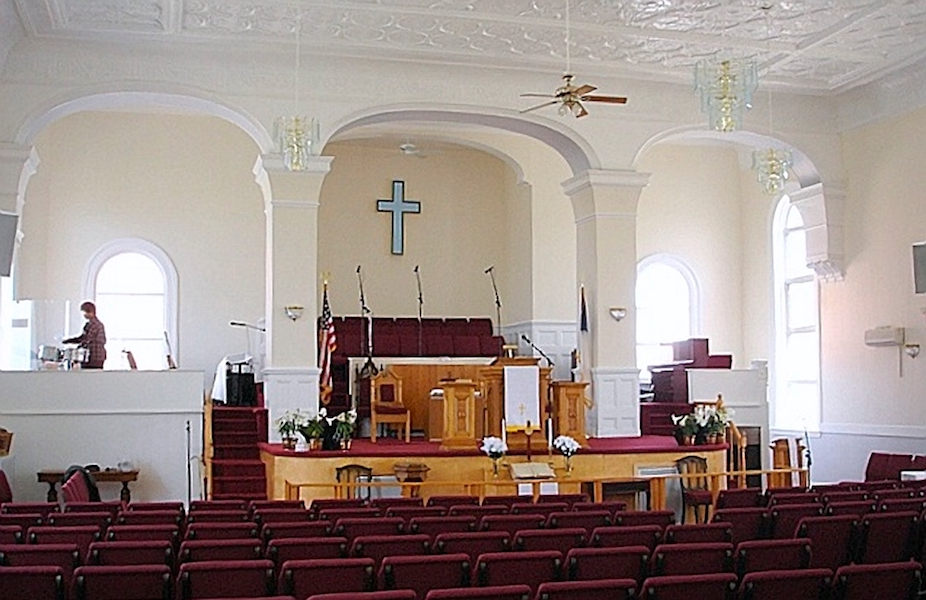 Interior of Trinity Church with wooden podium and altar in church with white walls and red pews