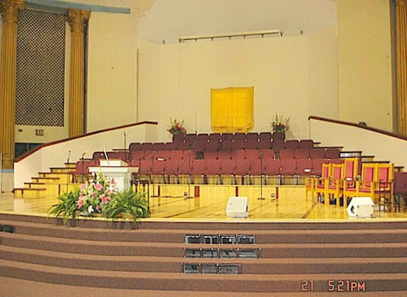 Completed podium for Triumphant COG church with red seats for choir