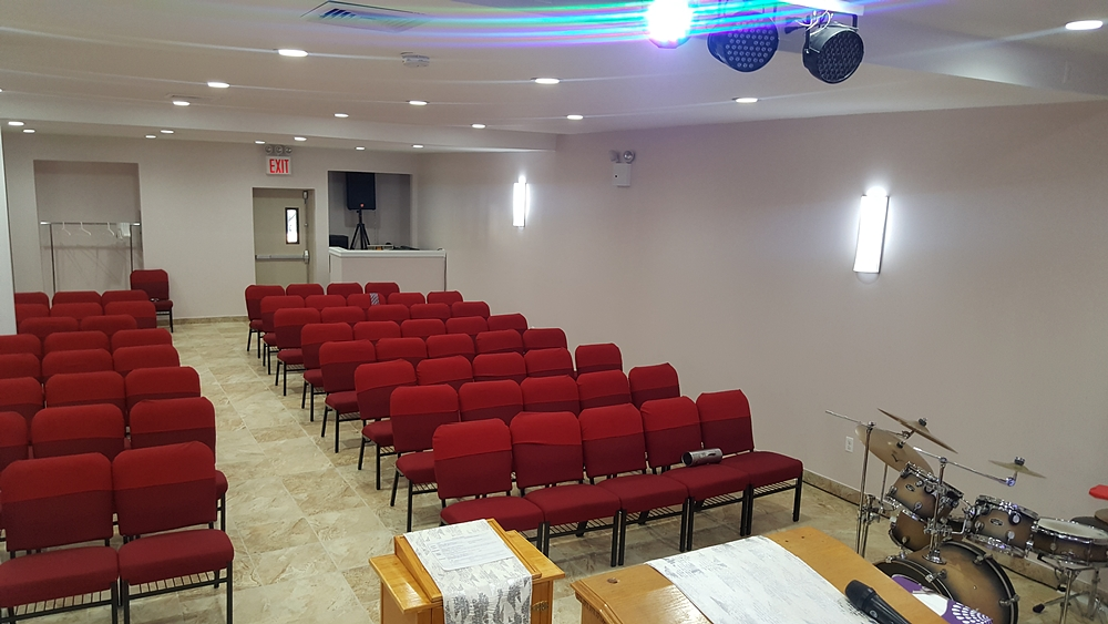 View of seating arrangement in Washington Avenue Church with red chairs