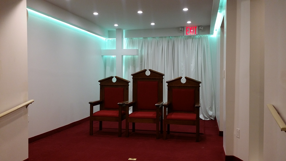 Front view of church with illuminated cross at the front and three chairs on podium