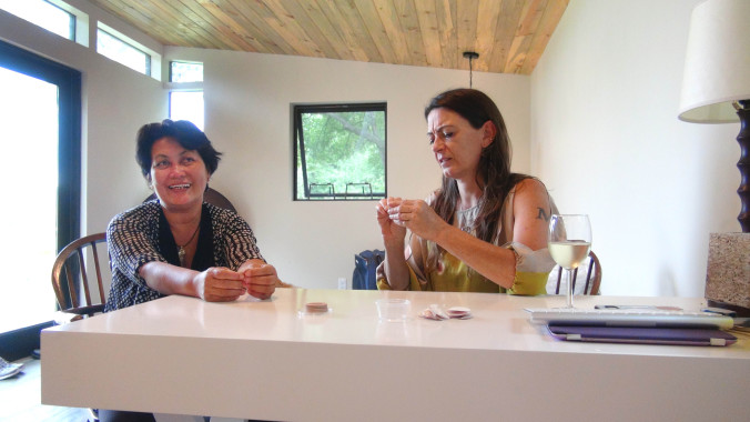 Hope and Micol record a video interview while peeling nipple stickers before the community dinner.
