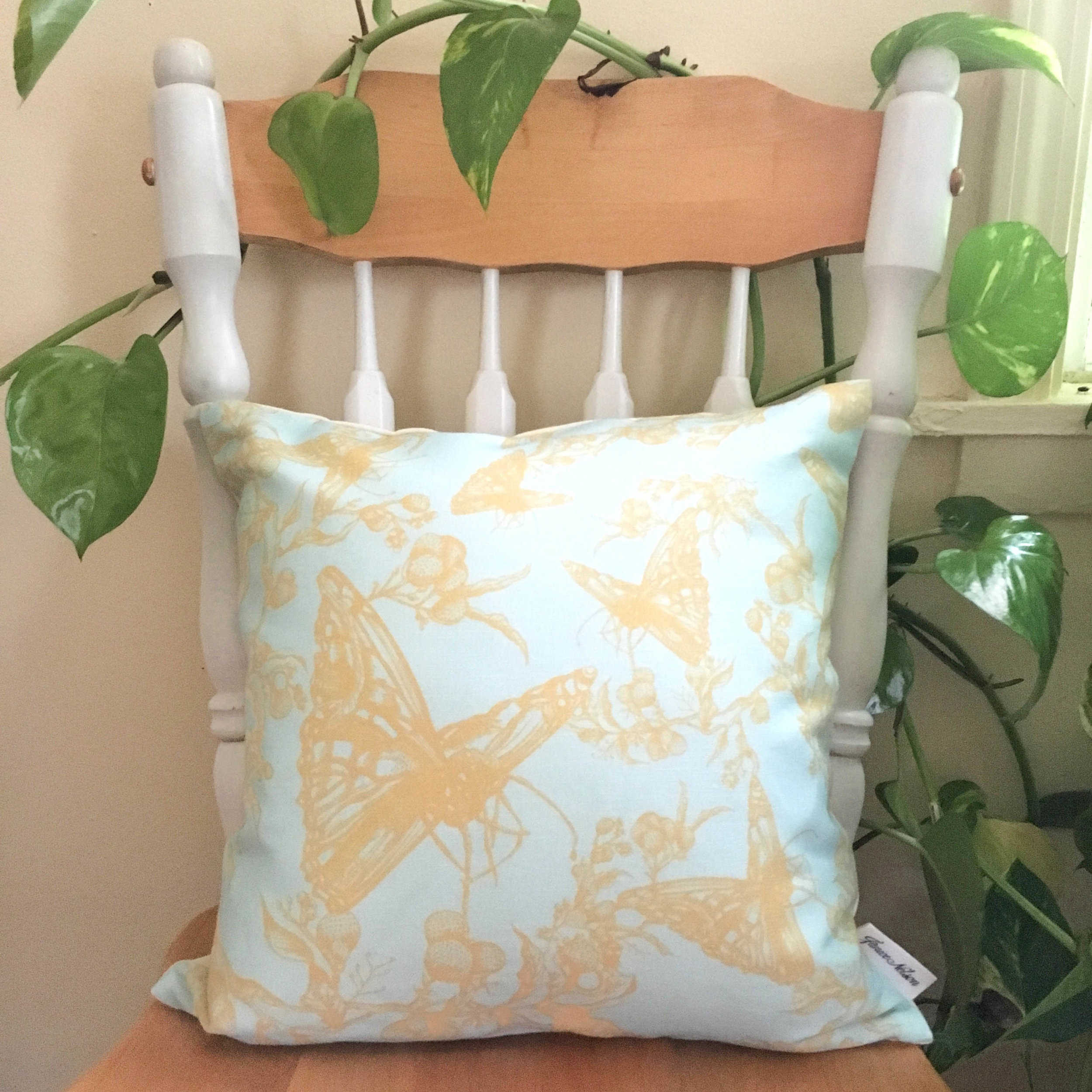 16x16 Cynthia Pillow with allover yellow butterfly pattern on chair