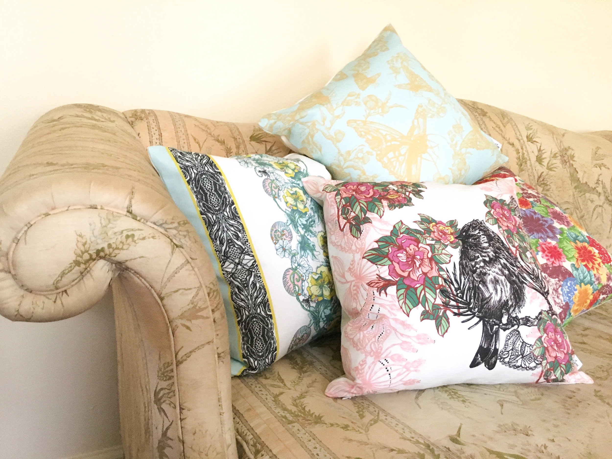 Acanthis Pillow, Cynthia Pillow, and Celandine Pillow piled on edge of a couch