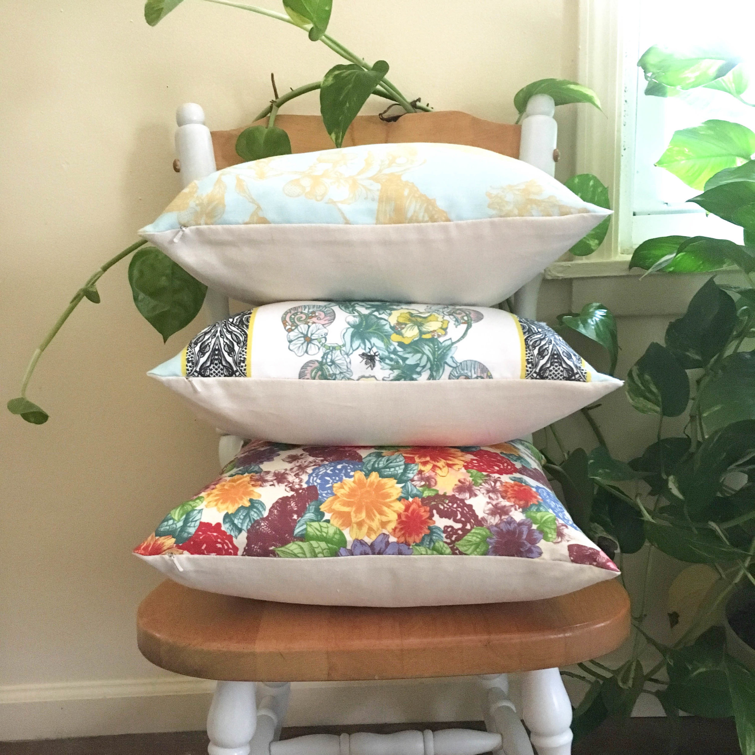 Sustainably made home decor pillow trio stacked on wooden chair next to plant