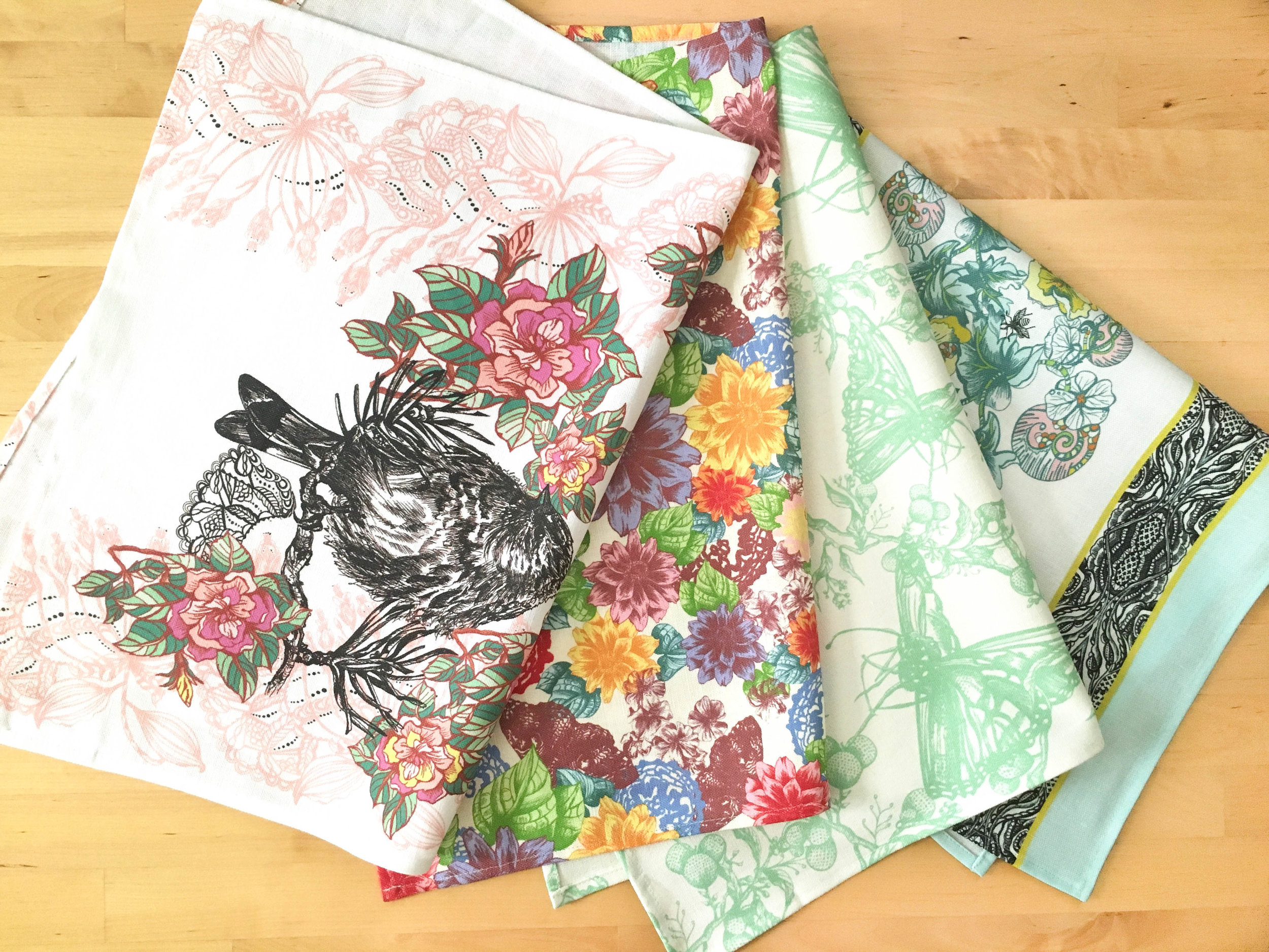Four Janice Nelson kitchen tea towels folded in half laying side by side