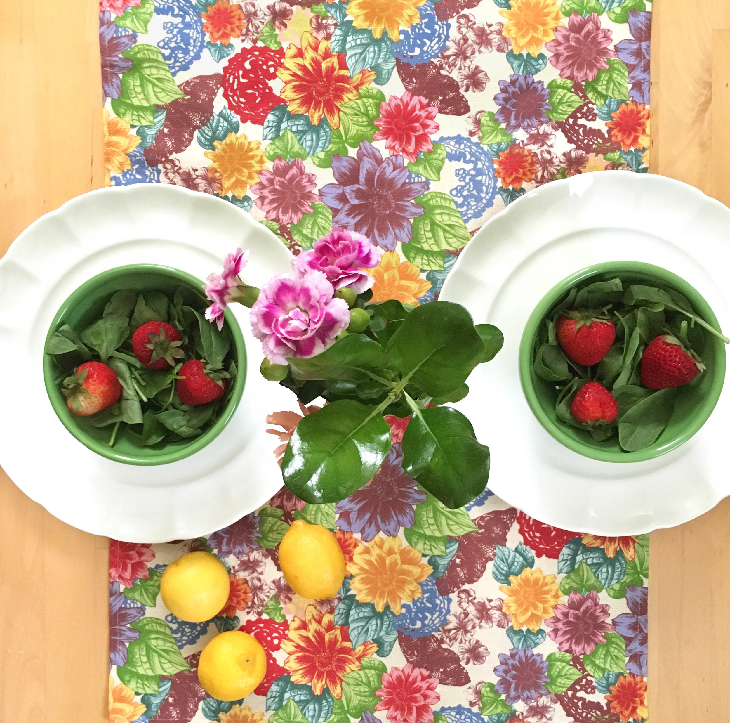 Unique and colorful Zale Table Runner in place setting with flowers, strawberries, and lemons