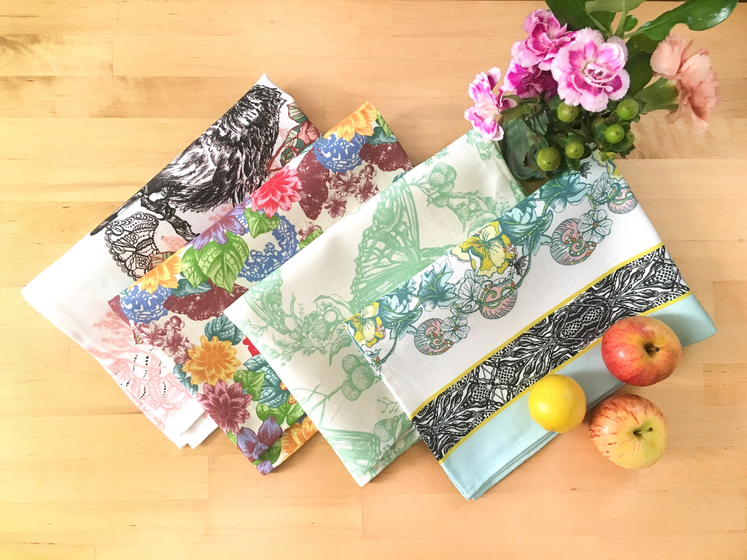 Made in the United States sustainable kitchen tea towels folded and placed with flowers