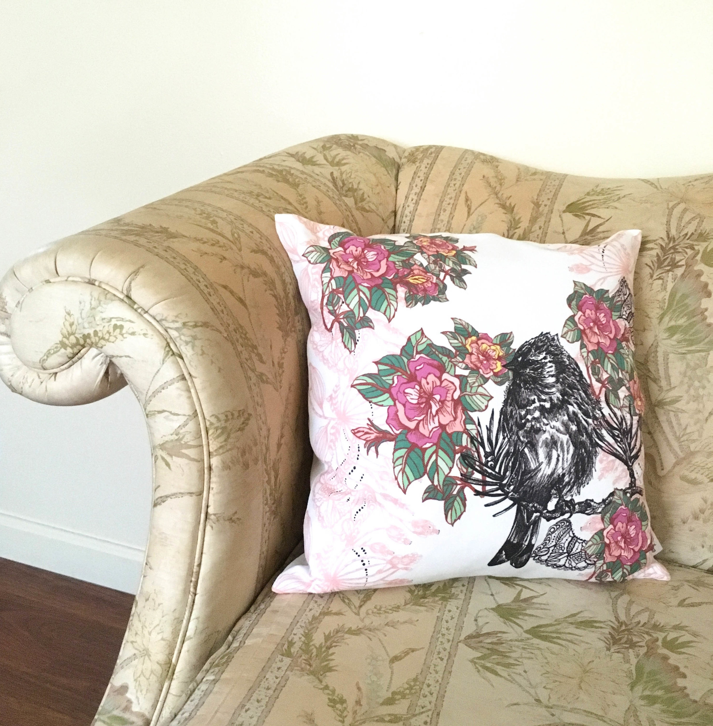 16x16 Acanthis Pillow with bright pink flowers and a bird on a branch displayed on sofa