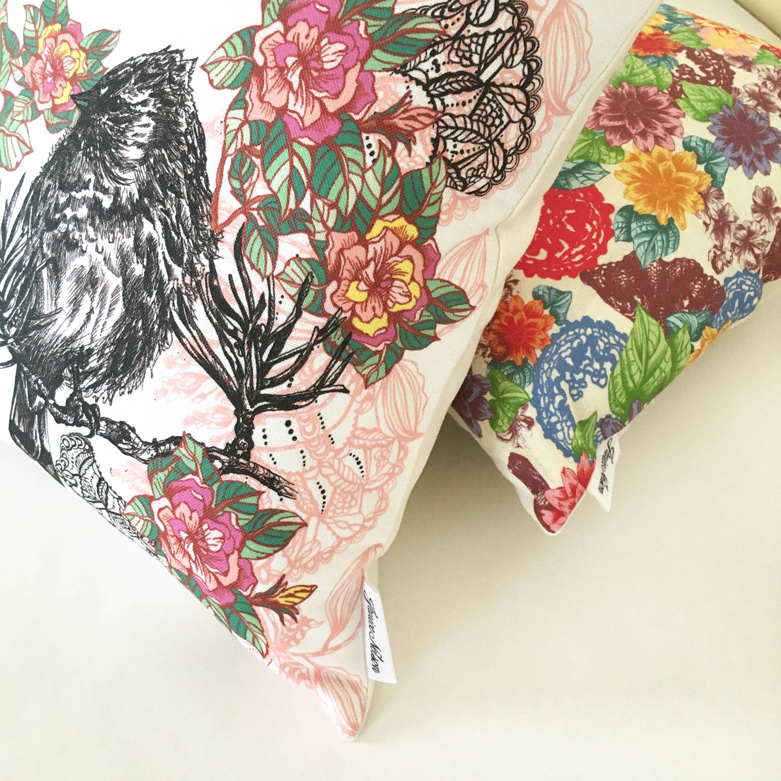 Janice Nelson's illustrative and detailed Acanthis bird pillow with bright pink and yellow flowers is shown sitting in front of a Zale pillow that is covered in an ornate allover floral pattern.