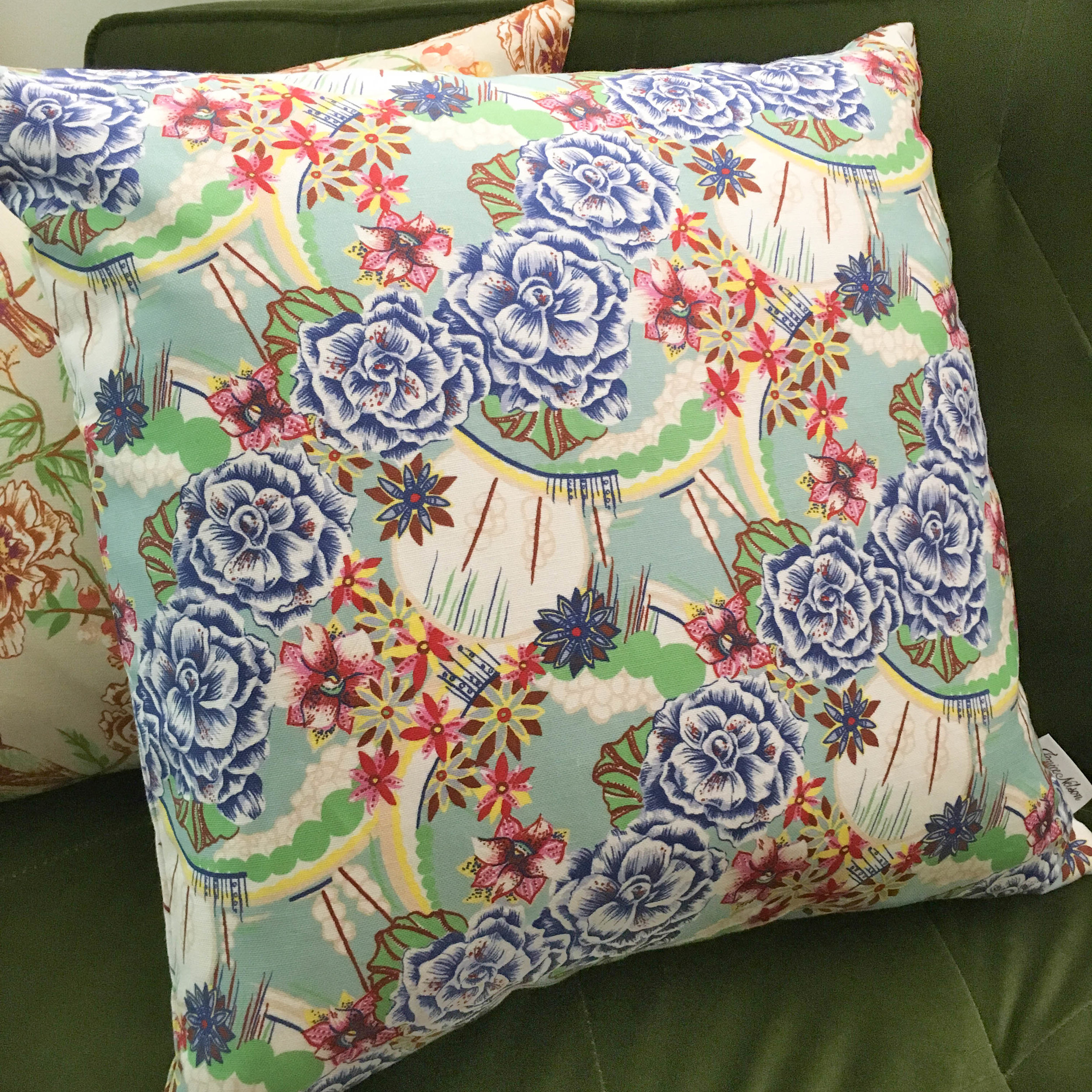 The 'Reverie' pillow is a bright and ornate textile design with cobalt blue begonias, pops of red and pink flowers, and sunburst-like line work that creates a daydream- like print.