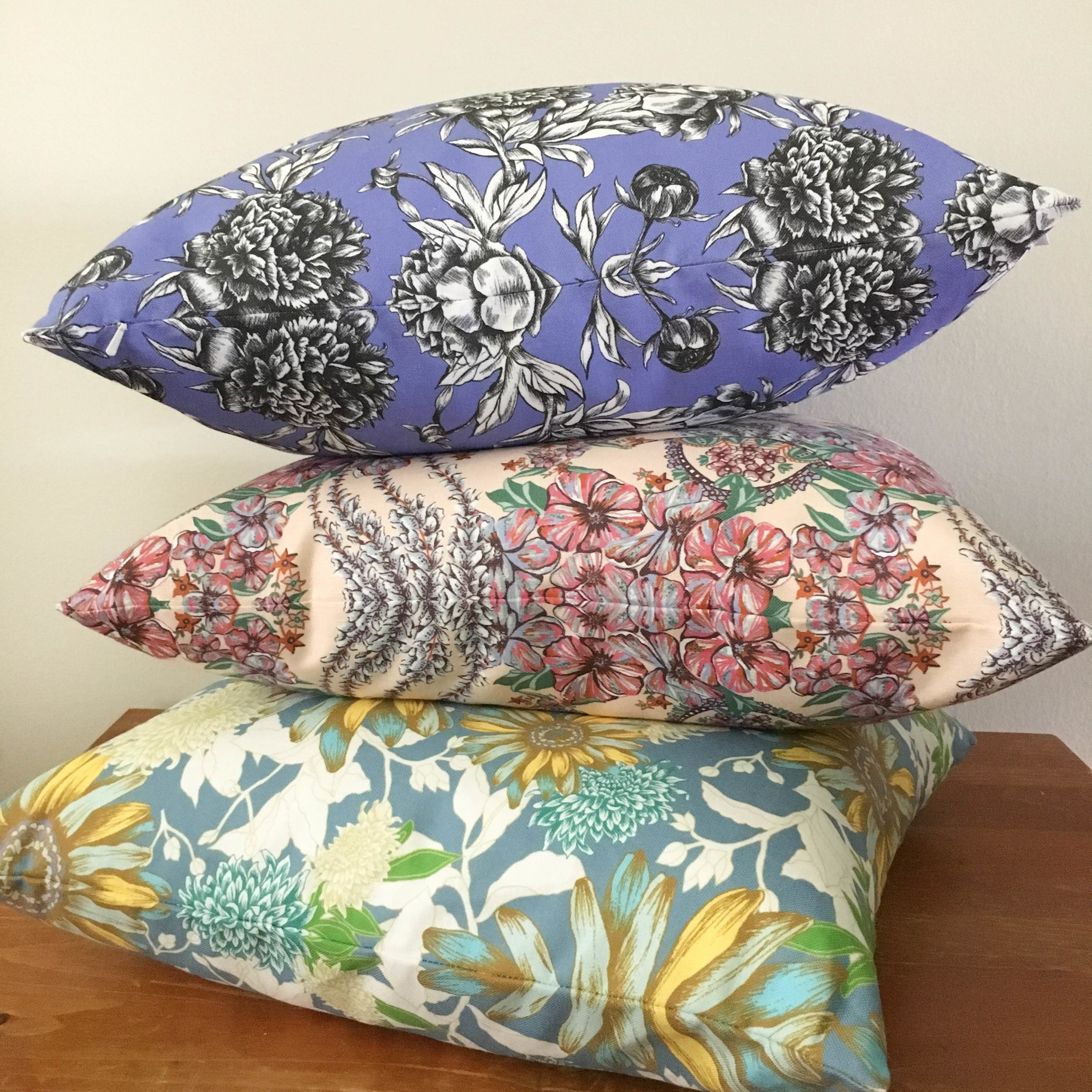 Paeonia, Viola, and Gerbera pillows are elegantly stacked to display their colorful, botanical painted line work