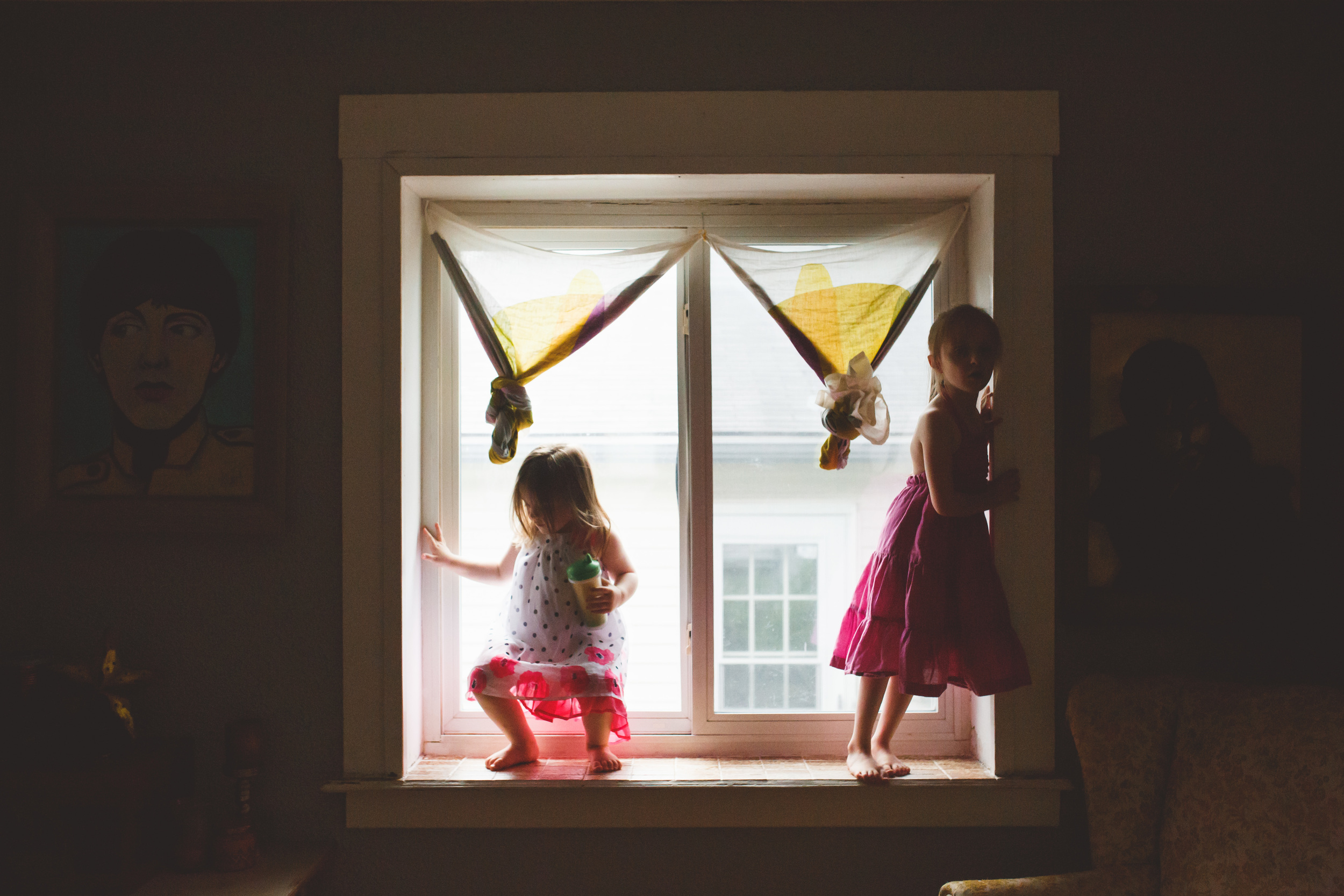 Two girls standing in a window.