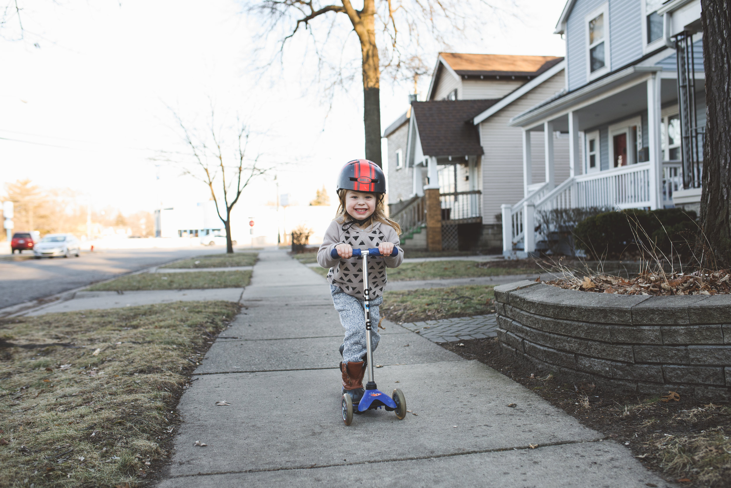 Little boy riding scooter.