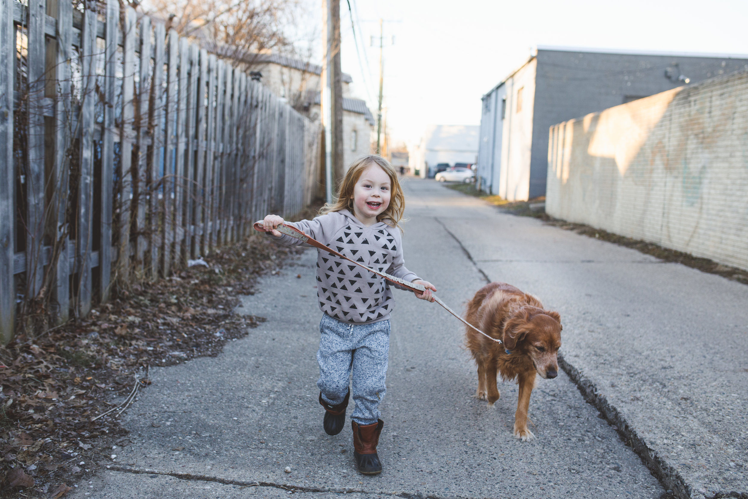 Little boy and dog in alley.
