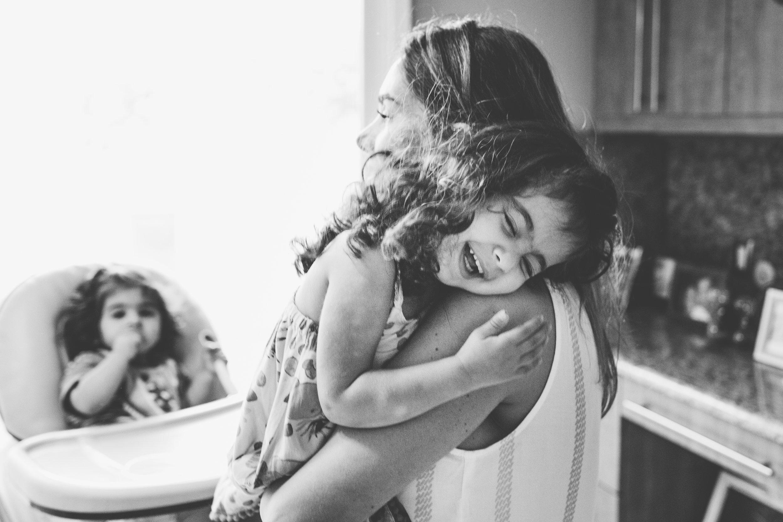 Daughter smiling over moms shoulder.
